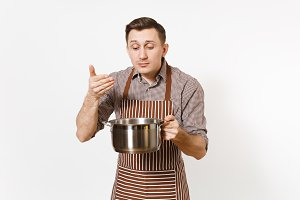 Man chef in striped brown apron holding silver stainless glossy aluminium empty stewpan, pan or pot isolated on white background. Male housekeeper or houseworker. Kitchenware, dishes, cuisine concept.
