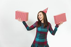 Beautiful smiling caucasian fun young happy woman in plaid dress and birthday party hat with two gift present boxes, celebrating and enjoying holiday on white background isolated for advertisement.
