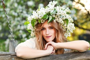 Portrait of young woman in lilac wreath.