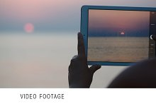 Taking pictures of sunset over sea