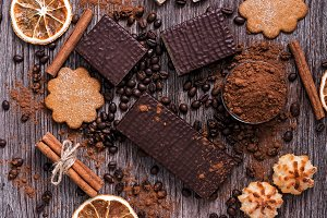 Confectionery products- chocolate wafers, cookies, coconut biscuits on a wooden table, top view.