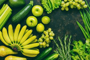 Assorted fresh green and yellow fruits and vegetables on a dark background, top view, copy space. assorted vegetables. The concept of healthy eating. Toned photo.