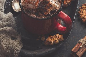 Hot chocolate with marshmallows and cookies with nuts. Cozy atmosphere, rustic style. Toned photo.