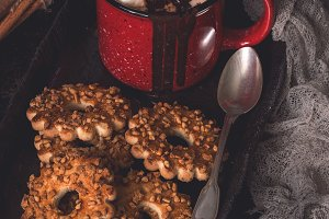Hot chocolate with marshmallow in a red mug and biscuits with nuts. Rustic style, dark photo with toning.
