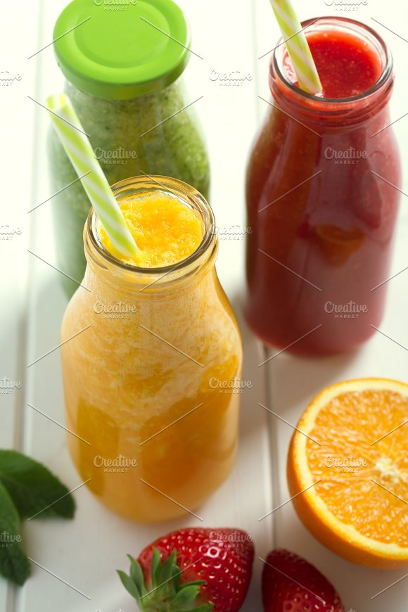 Fresh Orange Strawberry And Broccoli Smoothie In Bottles With Fruits And Vegetables On A White Wooden Rustic Background Closeup Shot