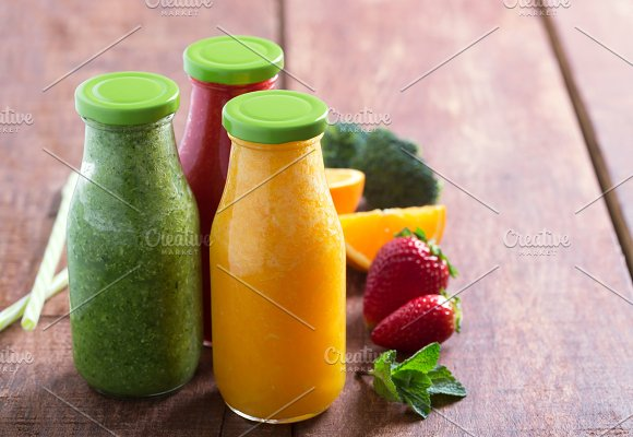 Fresh Strawberry Orange And Broccoli Smoothie In Bottles With Fruits And Vegetables On A Brown Wooden Rustic Background