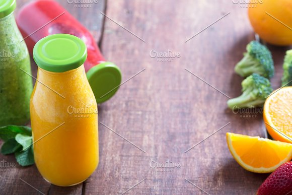 Fresh Strawberry Orange And Broccoli Smoothie In Bottles With Green Caps With Fruits And Vegetables On A Brown Wooden Rustic Background Copy Space In The Center
