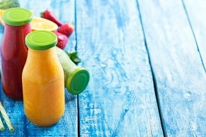 Fresh strawberry, orange and broccoli smoothie in bottles with fruits and vegetables on a blue wooden rustic background