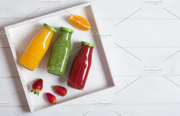 Fresh Orange Strawberry And Broccoli Smoothie In Bottles With Fruits And Mint In A White Wooden Rustic Box And On A White Background Copy Space For Text On The Right Side