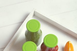 Fresh orange, strawberry and broccoli smoothie in bottles with green caps with fruits and mint in a white wooden rustic box and on a white background, vertical.
