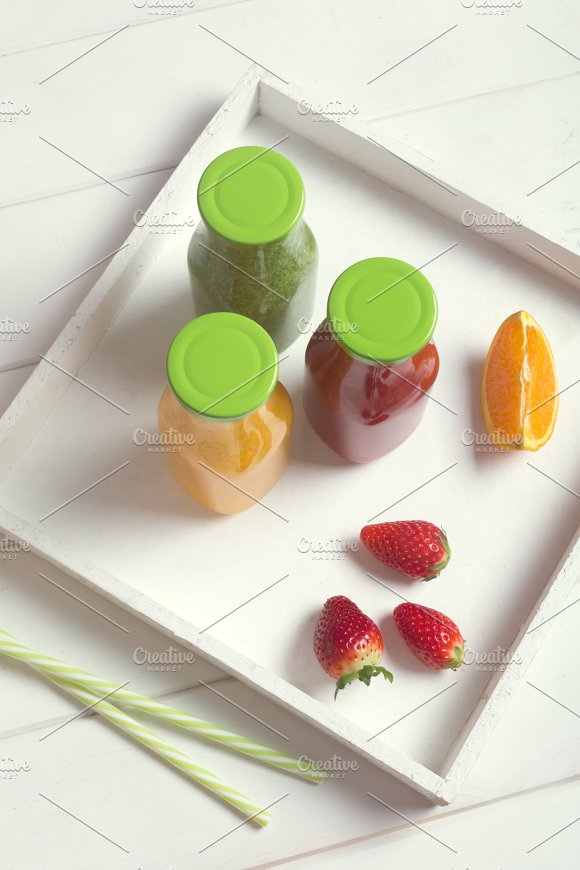Fresh Orange Strawberry And Broccoli Smoothie In Bottles With Green Caps With Fruits And Mint In A White Wooden Rustic Box And On A White Background Vertical
