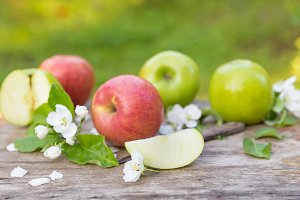 green red apples with flowers on wooden background