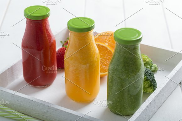 Fresh Strawberry Orange And Broccoli Smoothie In Three Bottles With Fruits And Vegetables On A White Wooden Rustic Background