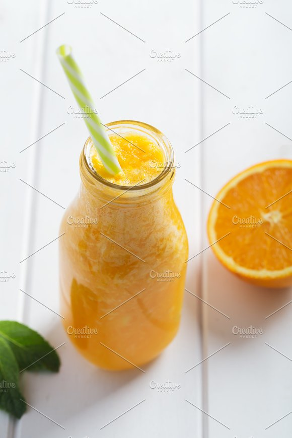 Fresh Orange Smoothie In Bottle On A White Wooden Rustic Background