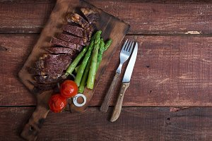 Grilled beef steak with vegetables on a wooden rustic background, with copy space