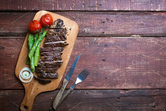 Grilled Beef Steak On A Cooking Board And Wooden Rustic Background
