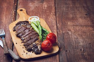 Grilled beef steak with asparaguas and tomatoes on a wooden rustic background