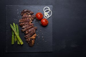 Grilled beef steak on a black background with copy space