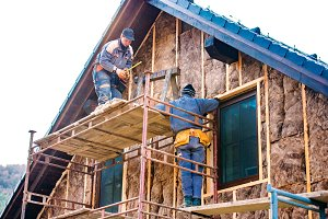 Construction workers thermally insulating house facade with glas