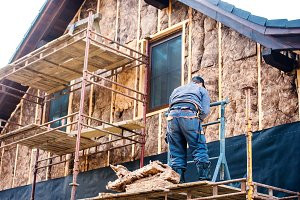 Construction worker thermally insulating house facade with glass