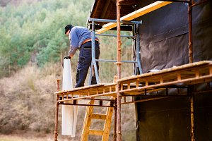 Construction worker on scaffold thermally insulating house, blac
