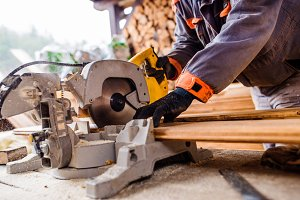 Carpenter working. Man cutting plank by circular saw.