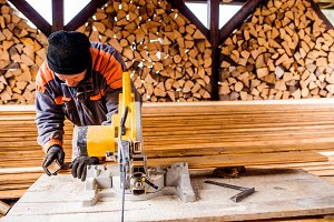 Carpenter working. Man cutting plank by circular saw.
