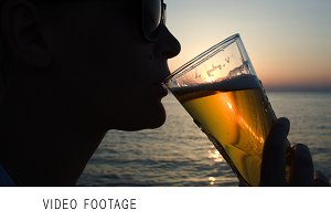 Woman drinking beer on beach sunset