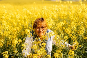 Senior woman in a field of yellow