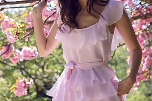 young sexy woman standing in pink dress next to sakura