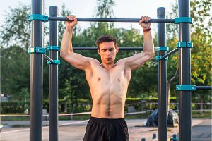 Young male athlete doing chin-up exercises in the park. Fitness man working out outside