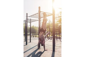 Young fit muscular man doing handstand Workout outdoors