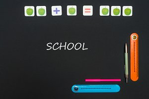 Black art table with stationery supplies with text school on blackboard