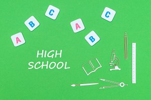 text high school, from above wooden minitures school supplies and abc letters on green background