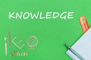 text knowledge, school supplies wooden miniatures, notebook on green background