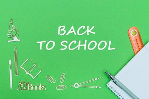 text back to school, school supplies wooden miniatures, notebook with ruler, pen on green backboard