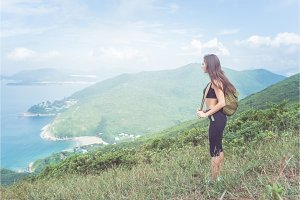 Backpack female traveler standing on hill looking at sea and mountains. Trail runner taking a break enjoying view of nature