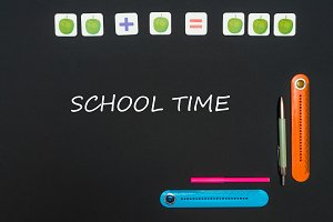 Black art table with stationery supplies with text school time on blackboard
