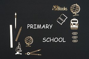 School supplies placed on black background with text primary school