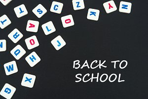 english colored square letters scattered on black background with text back to school