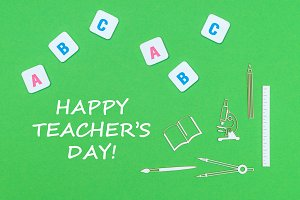 text happy teacher's day, from above wooden minitures school supplies and abc letters on green background