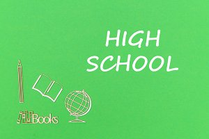 text high school, school supplies wooden miniatures on green background