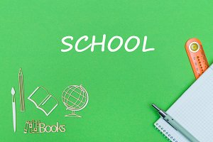 text school, school supplies wooden miniatures, notebook on green background