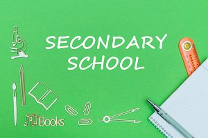 text secondary school, school supplies wooden miniatures, notebook with ruler, pen on green backboard