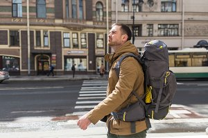 Young hipster man traveling backpacker outdoor. Travel concept.