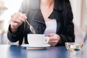 Woman stirs a spoonful of coffee