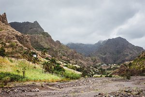Panorama of dried-up stream surrounded by fertile green valley and rugged cliffs. Lonely white dwelling on the hill. Santo Antao, Cabo Verde