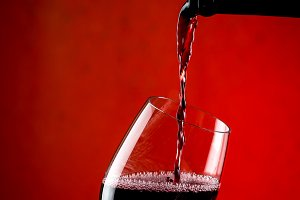 Pouring red wine into a glass, red background