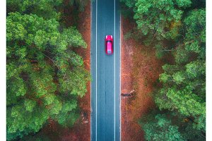 Aerial view of road with blurred car in green forest