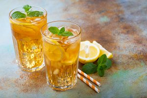 Traditional iced tea with lemon, mint and ice in tall glasses. Two glasses with cool summer drink on old rusty background